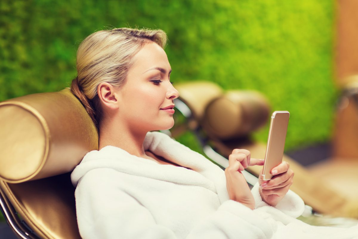 people, beauty, lifestyle, technology and relaxation concept - beautiful young woman in white bath robe with smartphone social networking at spa